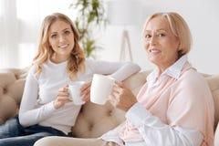 Mère et fille discutant la vie tout en buvant du thé Photos stock