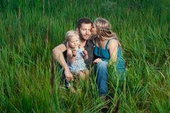 Mère et fille embrassant le papa dehors photo libre de droits