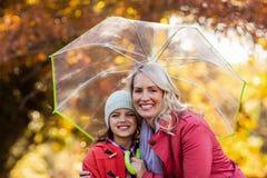 Mère et fille embrassant tout en tenant le parapluie Photos libres de droits