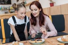 Mère et fille en café avec des desserts Photo stock
