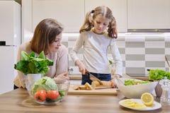 Mère et fille faisant cuire ensemble dans la cuisine à la maison, fille coupant le pain photo libre de droits