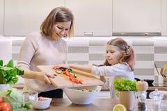 Mère et fille faisant cuire ensemble en salade végétale de cuisine photo stock