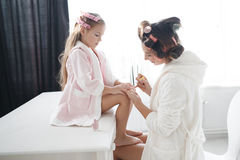Mère et fille faisant des cheveux et des manucures image stock
