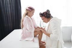 Mère et fille faisant des cheveux et des manucures images libres de droits