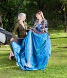 Mère et fille faisant la tente en parc à Photographie stock