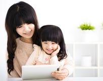 Mère et fille heureuses à l'aide du comprimé numérique Photo libre de droits