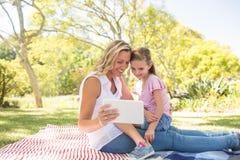 Mère et fille heureuses à l'aide du comprimé numérique dans le parc Photos stock