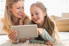Mère et fille heureuses à l'aide du comprimé numérique sur le plancher à la maison Image stock