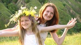 Mère et fille heureuses avec la guirlande de fleur banque de vidéos