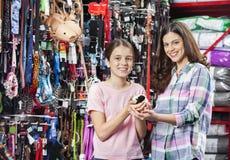 Mère et fille heureuses avec le cobaye dans le magasin d'animal familier Photos libres de droits