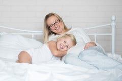 Mère et fille heureuses dans le lit Images stock
