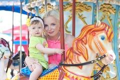 Mère et fille heureuses sur le carrousel Photo stock