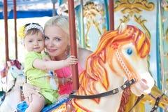Mère et fille heureuses sur le carrousel Image libre de droits