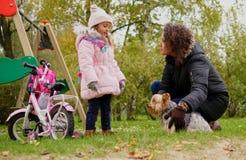 Mère et fille jouant avec le chien sur le terrain de jeu Images libres de droits