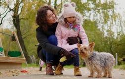 Mère et fille jouant avec le chien sur le terrain de jeu Photos libres de droits