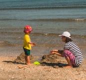 Mère et fille jouant avec le sable sur la plage Photo libre de droits