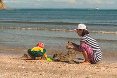 Mère et fille jouant avec le sable sur la plage Image stock