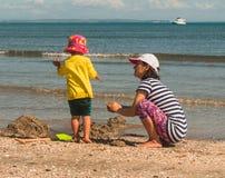 Mère et fille jouant avec le sable sur la plage Photographie stock
