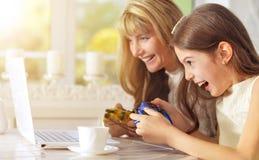 Mère et fille jouant le jeu d'ordinateur Image stock