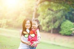 Mère et fille jouant le moulin à vent en parc Images libres de droits