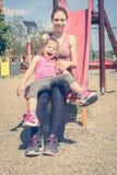 Mère et fille jouant sur la glissière dans le terrain de jeu Photographie stock
