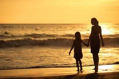 Mère et fille jouant sur la plage au temps de coucher du soleil Images stock