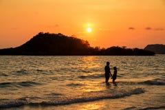 Mère et fille jouant sur la plage au temps de coucher du soleil Photos libres de droits