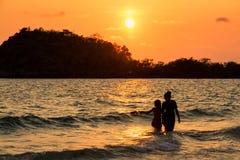 Mère et fille jouant sur la plage au temps de coucher du soleil Photographie stock