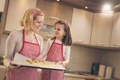 Mère et fille jugeant la pizza prête pour la cuisson Photographie stock libre de droits