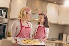 Mère et fille jugeant la pizza prête pour la cuisson images libres de droits