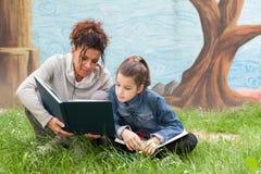 Mère et fille lisant un livre Images stock