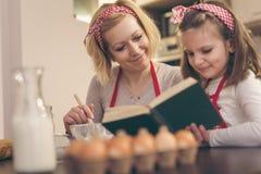 Mère et fille lisant un livre de cuisine Images libres de droits