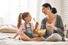Mère et fille mangeant de la salade Photographie stock libre de droits