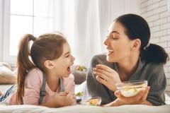 Mère et fille mangeant de la salade Photos stock