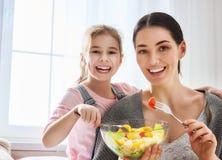 Mère et fille mangeant de la salade Photo stock