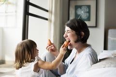 Mère et fille mangeant la carotte ensemble Image stock