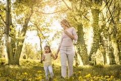 Mère et fille marchant dans le pré et mangeant la crème glacée  Image libre de droits