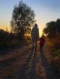 Mère et fille marchant sur la route de campagne au coucher du soleil Images stock
