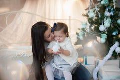 Mère et fille près d'un arbre de Noël, vacances, cadeau, décor, nouvelle année, Noël, mode de vie Photographie stock libre de droits