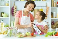 Mère et fille préparant le petit déjeuner Photo stock
