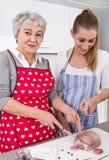Mère et fille préparant le repas ensemble : porc Photographie stock libre de droits