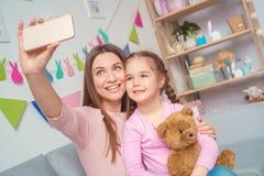 Mère et fille prenant ensemble à la maison des photos sur le smartphone Image stock