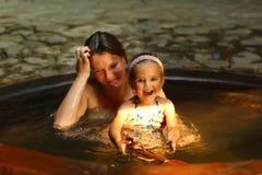 Mère et fille prenant le bain de courant ascendant de station thermale image stock
