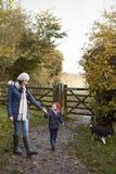 Mère et fille prenant le chien pour la promenade dans le paysage d'automne Photo libre de droits