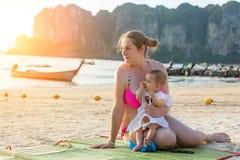 Mère et fille prenant un bain de soleil sur la plage tropicale Ils regardent en direction du coucher du soleil et l'apprécient image libre de droits