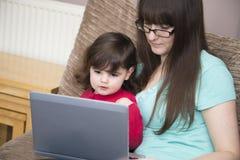 Mère et fille regardant en ligne Images stock