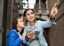 Mère et fille regardant le guide dans le téléphone image stock
