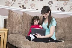 Mère et fille regardant sur les sites du réseau sociaux Images libres de droits