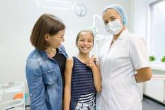 Mère et fille rendant visite au dentiste pédiatrique aux cliniques dentaires image libre de droits