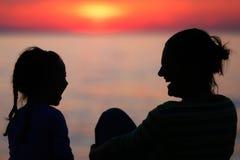 Mère et fille riant du coucher du soleil Images stock